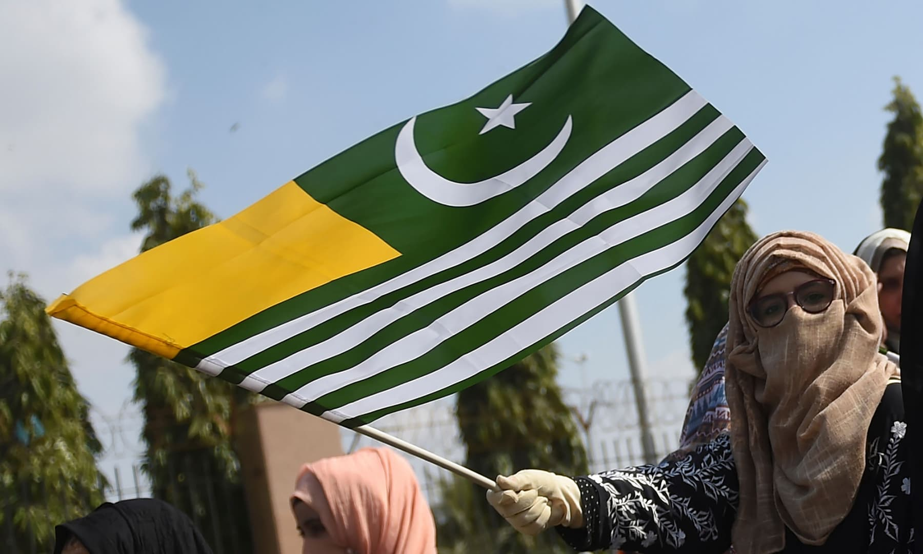 A protester waves the AJK flag at a demonstration to show solidarity with Kashmiris in Karachi on February 4, 2020. — AFP