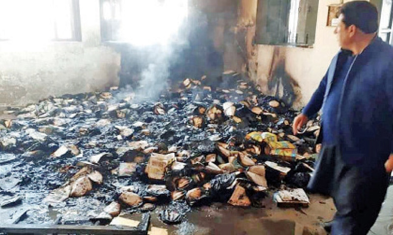 An official of the education department looks at the burnt books. — Dawn