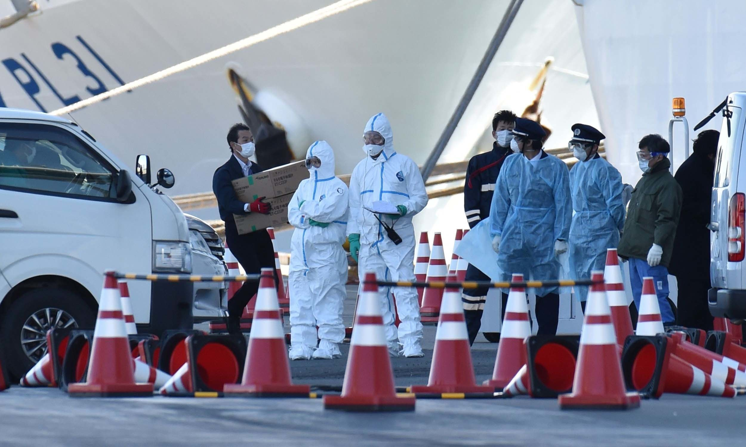 Personnel clad in protective gears and tasked to provide care for suspected patients on board the Diamond Princess cruise ship, prepare to carry out patients at the Daikoku Pier Cruise Terminal in Yokohama on February 6 after bringing patients from the ship. — AFP