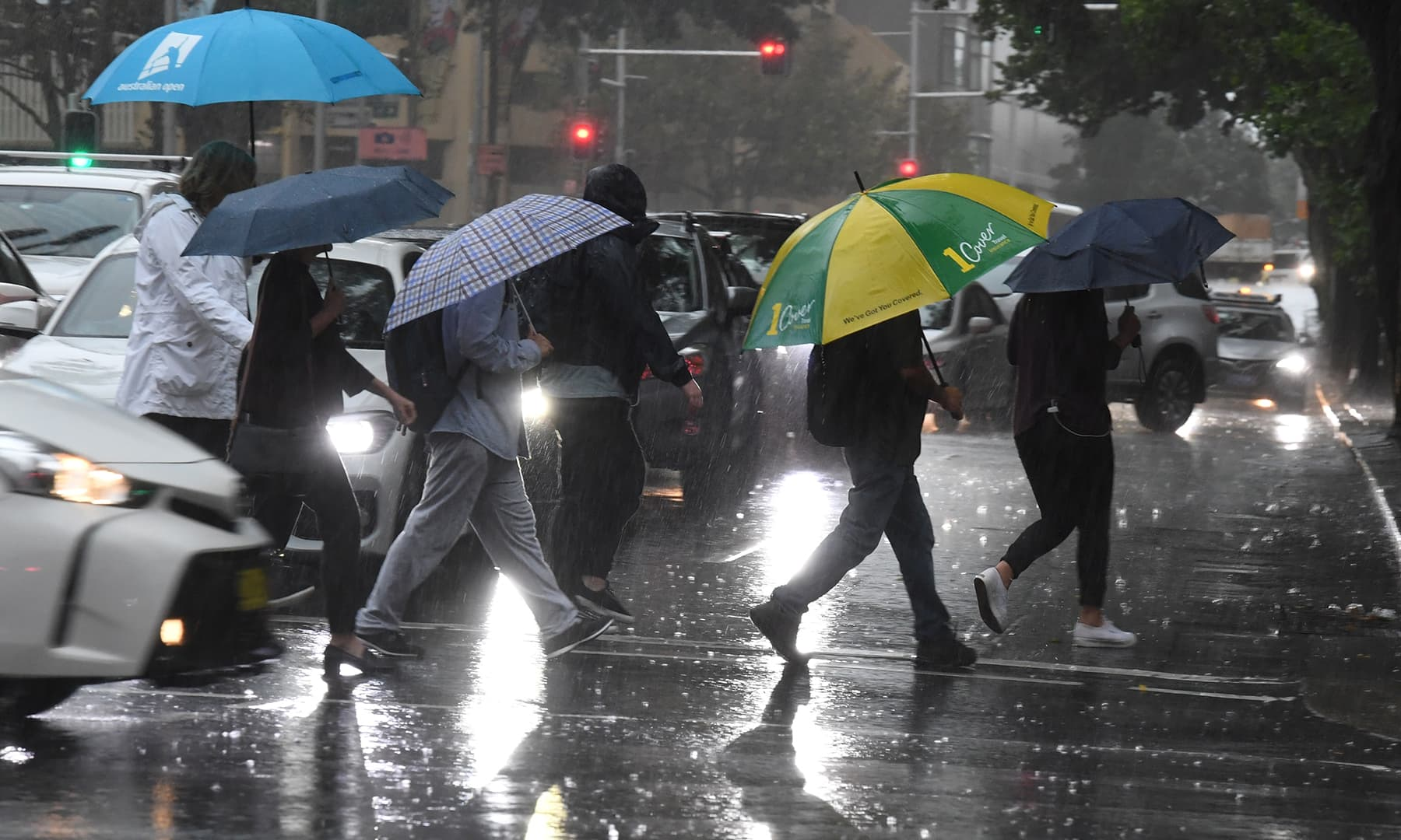 Pedestrians hold umbrellas during wet weather in Sydney on February 7. — Reuters