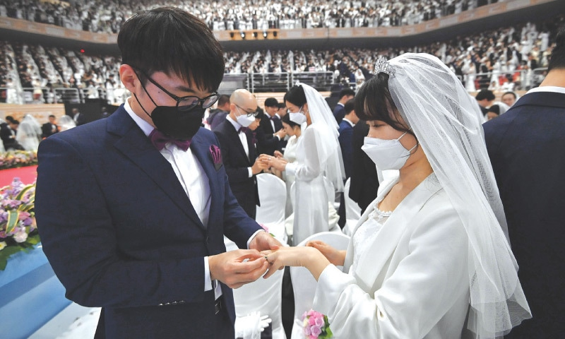 Gapyeong: Couples wearing protective face masks attend a mass wedding ceremony organised by the Unification Church on Friday.—AFP