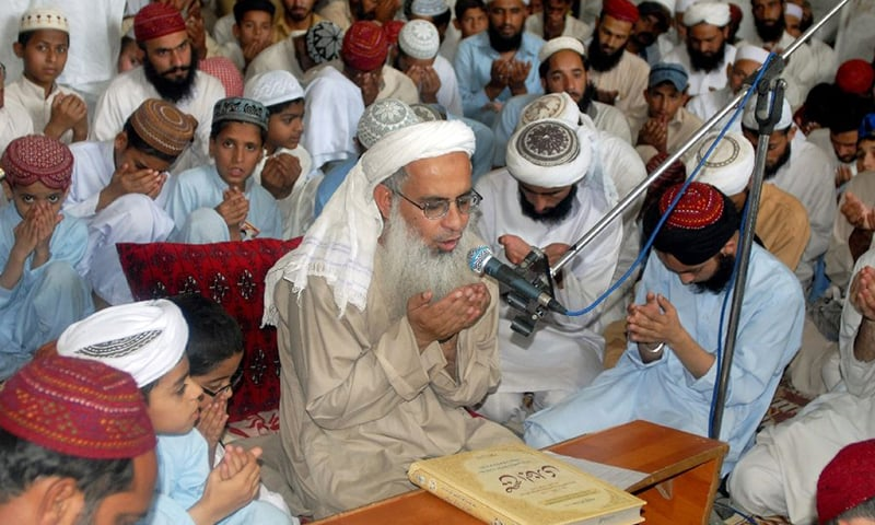 Maulana Abdul Aziz (C), flanked by followers, prays for those who were killed in the July 2007 military operation in Islamabad, in July 2009. — AFP/File