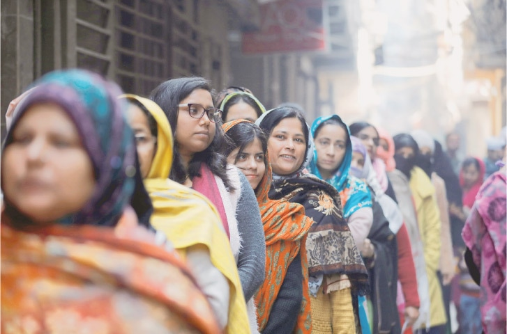 Women stand in a queue as they wait to cast their vote outside a polling booth during the state assembly election in Shaheen Bagh area of New Delhi on Saturday.—Reuters