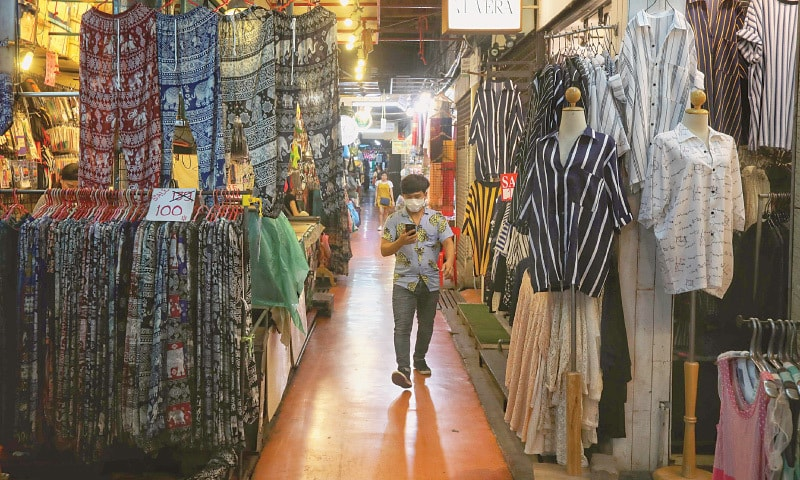 A man wearing a facemask walks past empty stalls at the Chatuchak weekend market in Bangkok on Saturday, as the number of tourists visiting the city has dropped considerably.—AFP