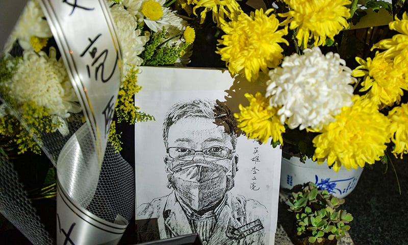 This photo taken on February 7, 2020, shows a photo of the late ophthalmologist Li Wenliang with flower bouquets at the Houhu Branch of Wuhan Central Hospital in Wuhan in China's central Hubei province. — AFP