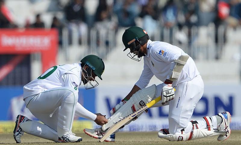 Pakistan's Abid Ali (L) helps Bangladesh's batsman Saif Hassan during the third day of the first cricket Test match between Pakistan and Bangladesh at the Rawalpindi Cricket Stadium on February 9. — AFP