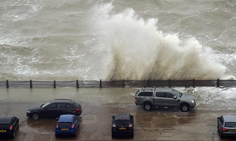 People sit in their cars to watch as they waves crash over the wall at Newhaven Harbour on the south coast of England on February 9, 2020, as Storm Ciara swept over the country. — AFP