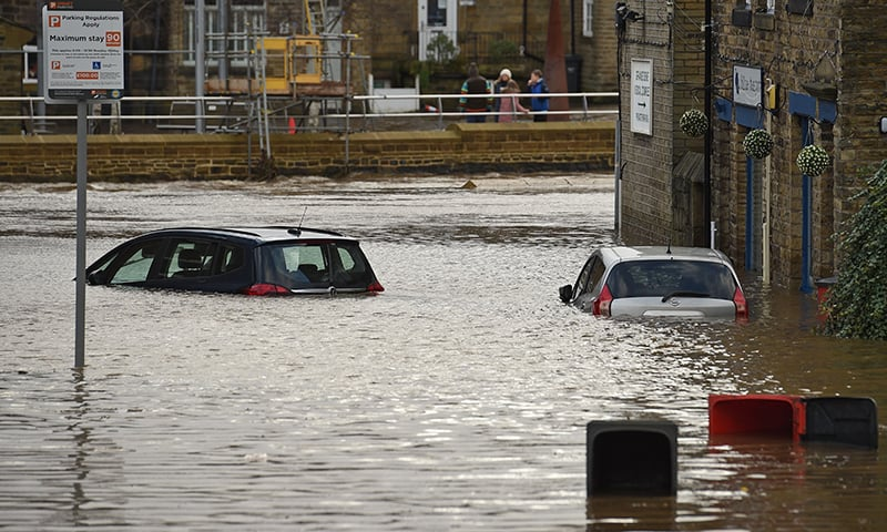 Cars are seen submerged as flood water covers the roads and car parks in Mytholmroyd, northern England, on February 9, 2020, after the River Calder burst its banks as Storm Ciara swept over the country. — AFP