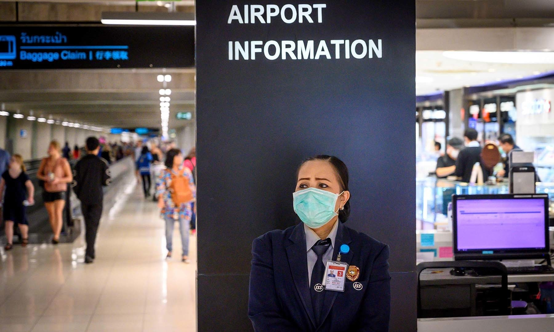 An airport staff member wearing a protective facemask stands at an information desk at Suvarnabhumi International Airport in Bangkok on February 9, 2020. - The new coronavirus that emerged in central China at the end of last year has killed more than 800 people and spread around the world. (Photo by Mladen ANTONOV / AFP)