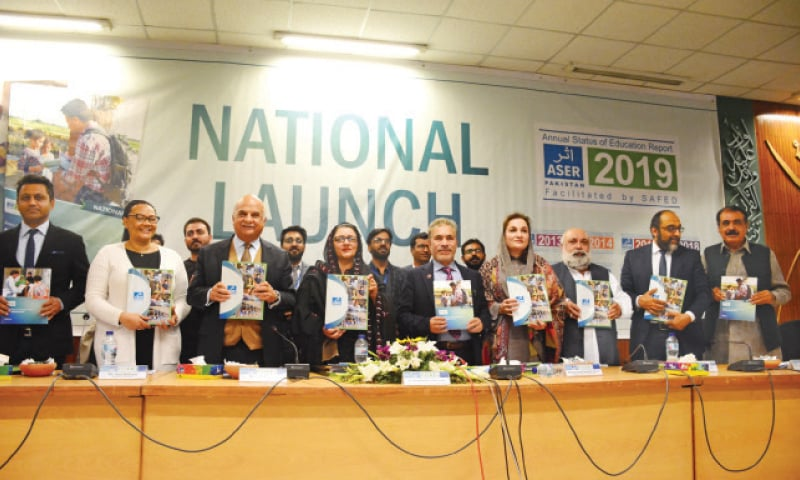 Participants hold the Annual Status of Education Report  during its launch on Monday. — Photo by Tanveer Shahzad