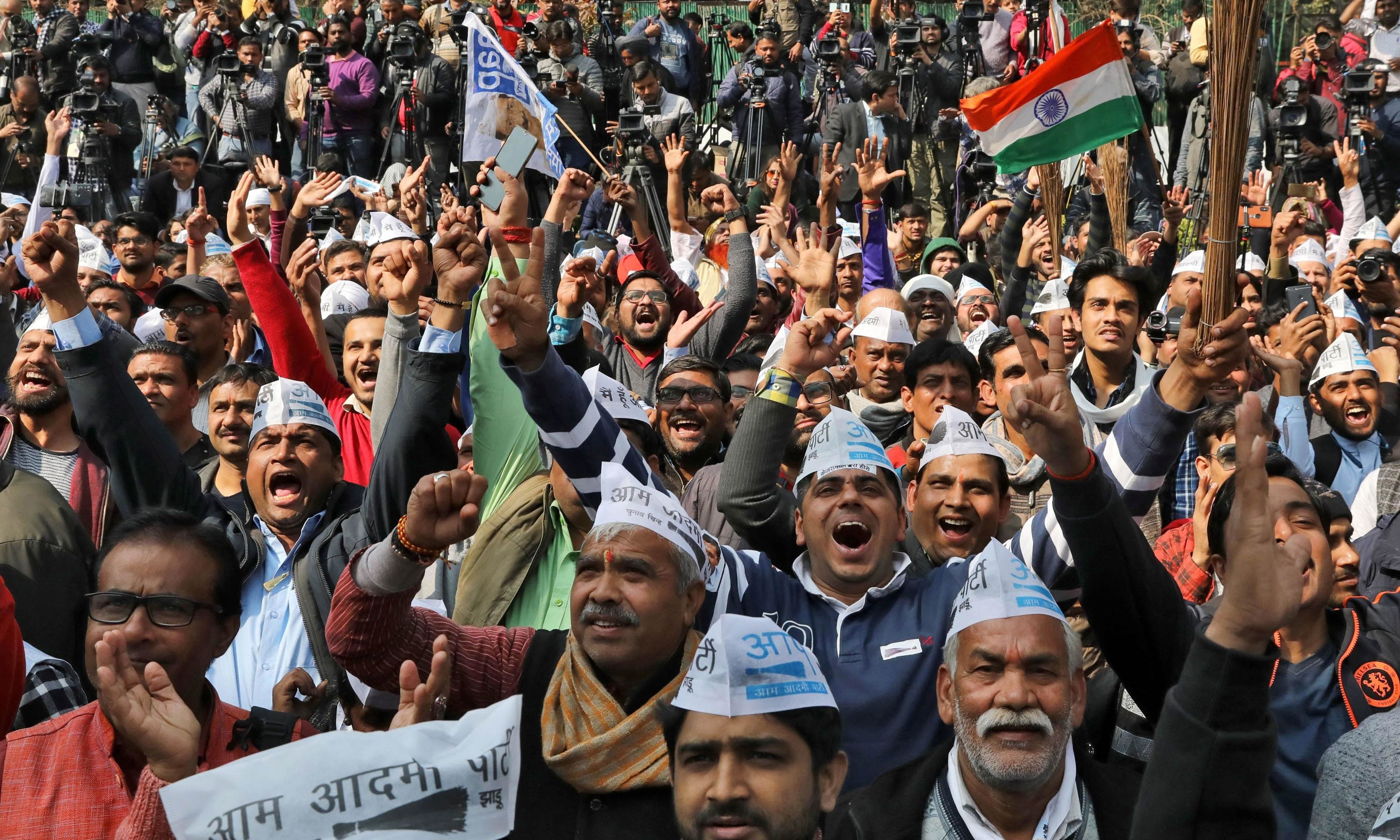 Supporters of Aam Aadmi Party celebrate after learning of the initial poll results outside its party headquarters in New Delhi on Feb 11. — Reuters