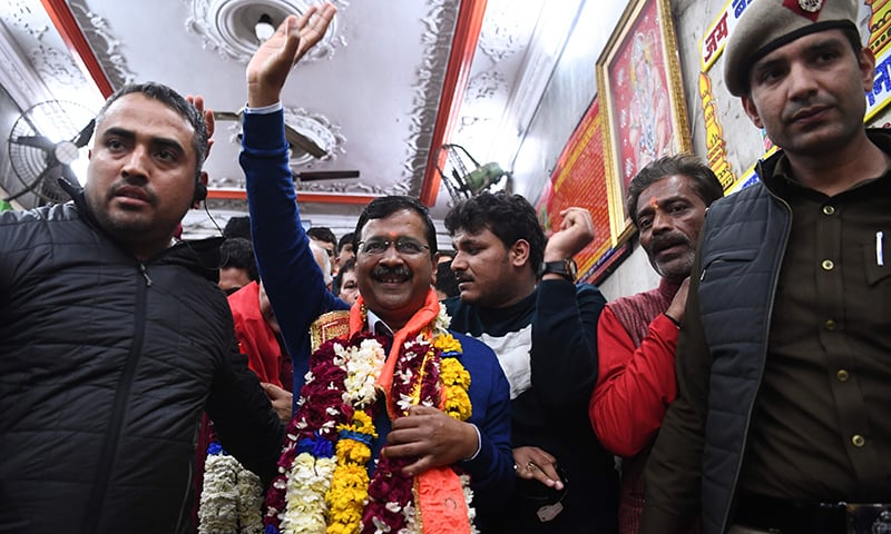 AAP chief Arvind Kejriwal (C) waves after paying his respect at the Hanuman Temple in New Delhi on February 11. — AFP