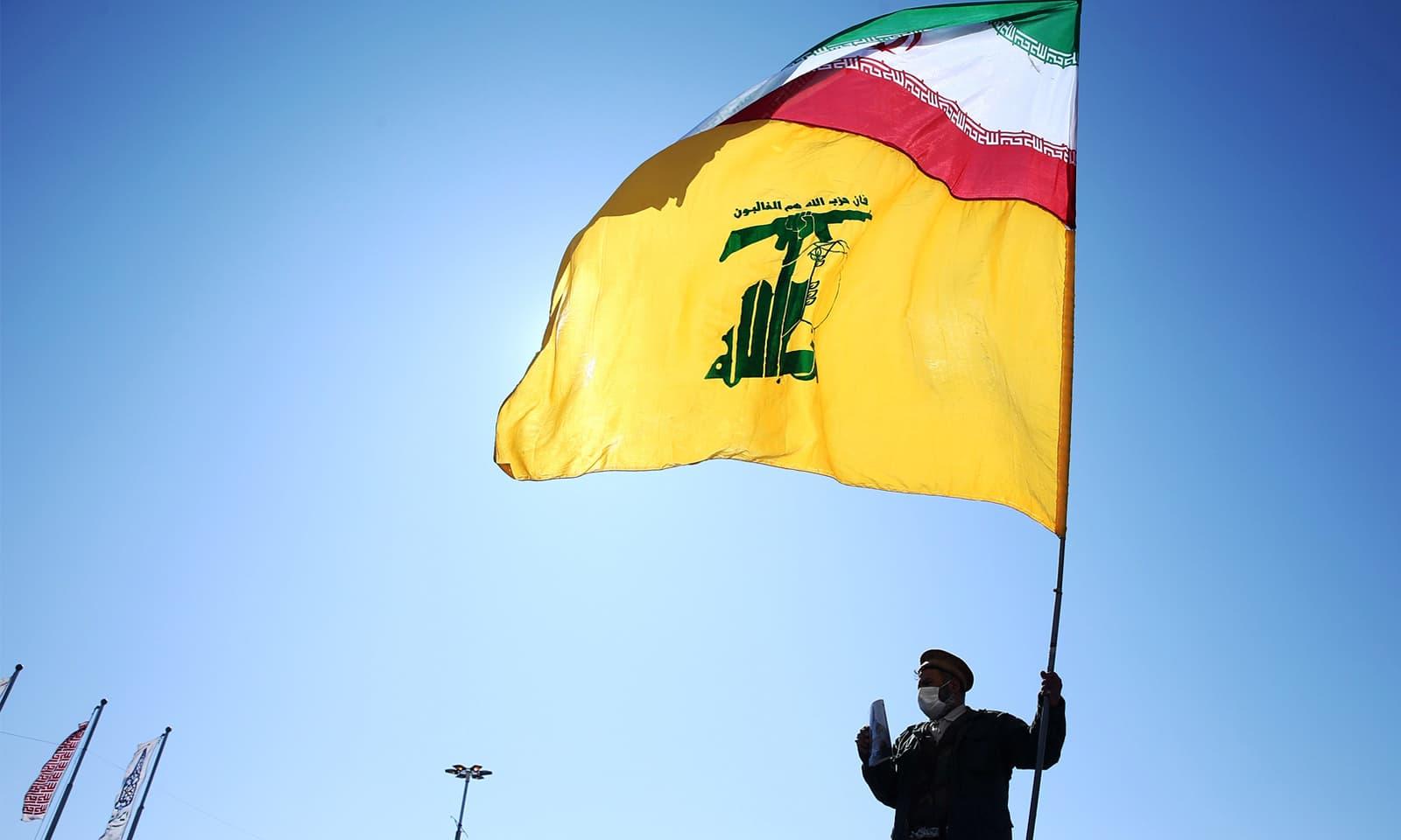 ایک شخص ایران کی القدس فورس کا جھنڈا تھامے کھڑا ہے—فوٹو: رائٹرز