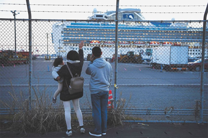 Yokohama (Japan): Relatives of passengers wave towards the Diamond Princess cruise ship, with 3600 passengers quarantined because of the coronavirus, as it departs Yokohama to dump waste water and generate potable water.—AFP