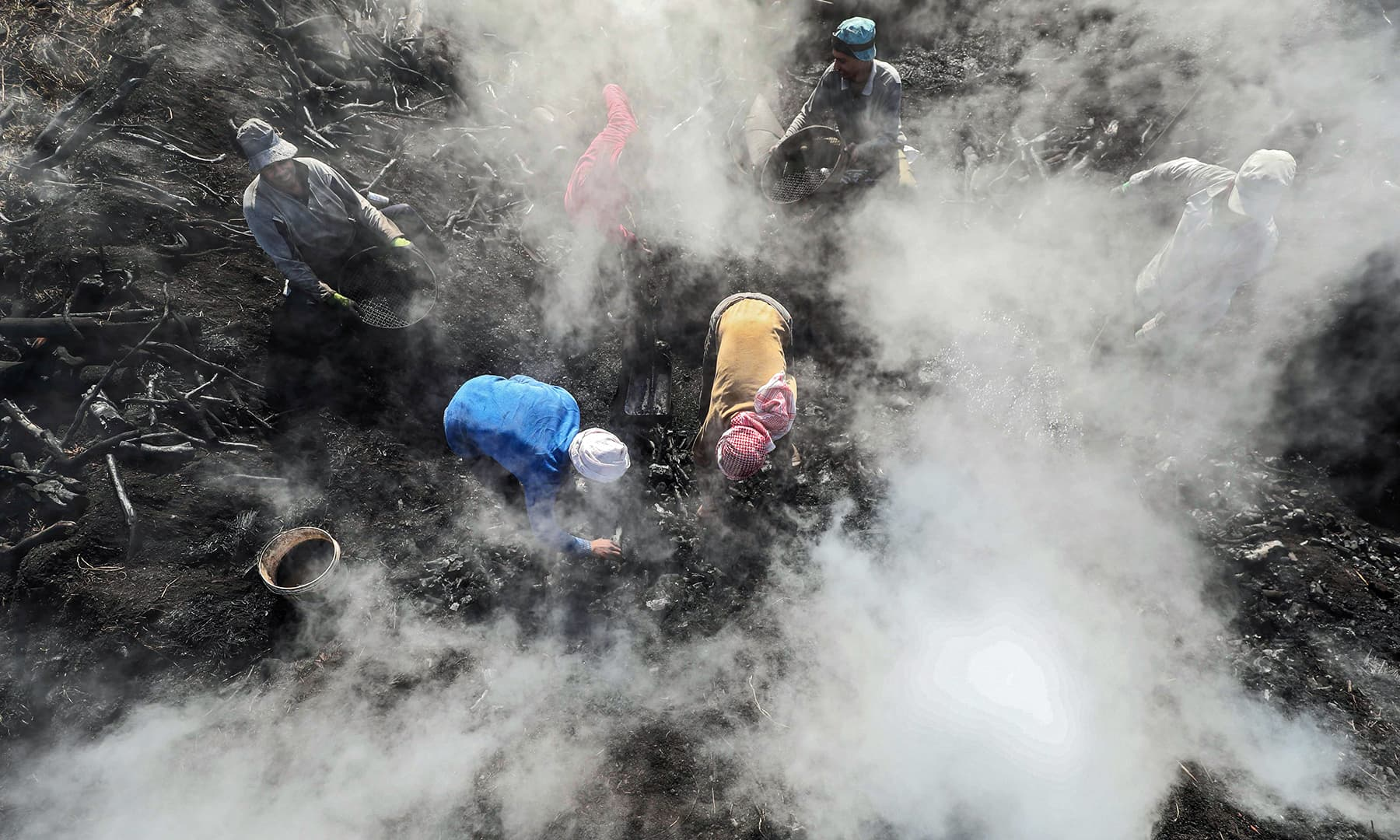 Egyptian labourers work at a charcoal factory in Egypt's Sharkia governorate. — AFP