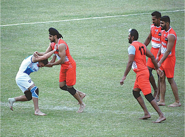 FAISALABAD: Players of Azerbaijan and Canada in action during their Kabaddi World Cup match at the Iqbal Stadium.—APP