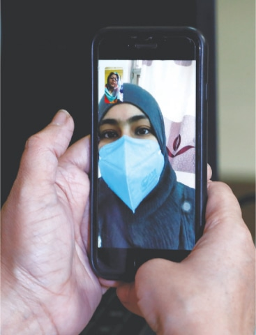 MAHAM Ali Khan, a student who went to China to collect her degree and now can't return after the virus outbreak, is seen on a mobile phone during a video call with her mother in Karachi on Feb 6.—Reuters