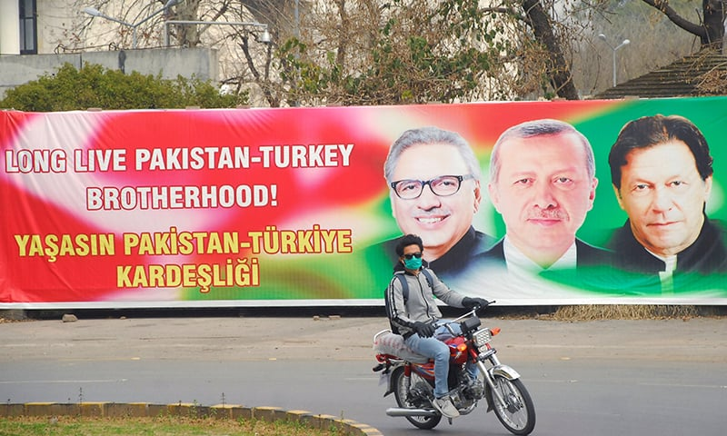 A man rides on a motorbike passing a sign showing President Arif Alvi, Turkish President Tayyip Erdogan and Prime Minister Imran Khan, in Islamabad, February 13. — Reuters