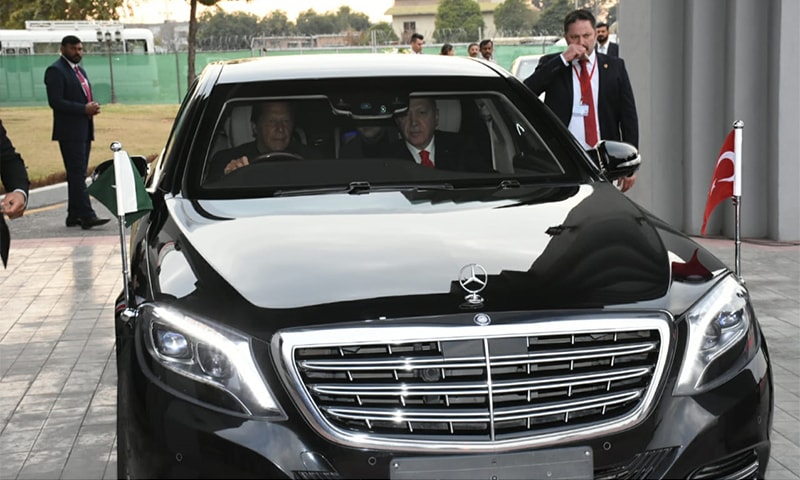 PM Imran Khan drives the Turkish president and first lady from the airport. — Courtesy: PM Office