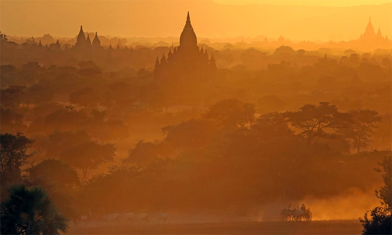 In this picture taken on February 3, 2014, people are transported on cattle drawn cart as they pass in front of the ancient pagodas at Bagan, Myanmar. — AFP/File