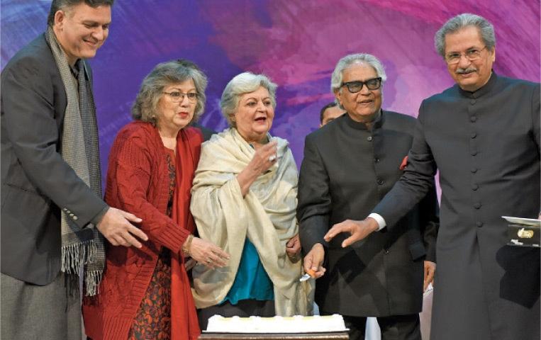 Muneeza Hashmi, Saleema Hashmi, poet Iftikhar Arif and Minister for Federal Education Shafqat Mehmood after cutting a cake on Faiz Ahmed Faiz' birth anniversary on Thursday. — Tanveer Shahzad