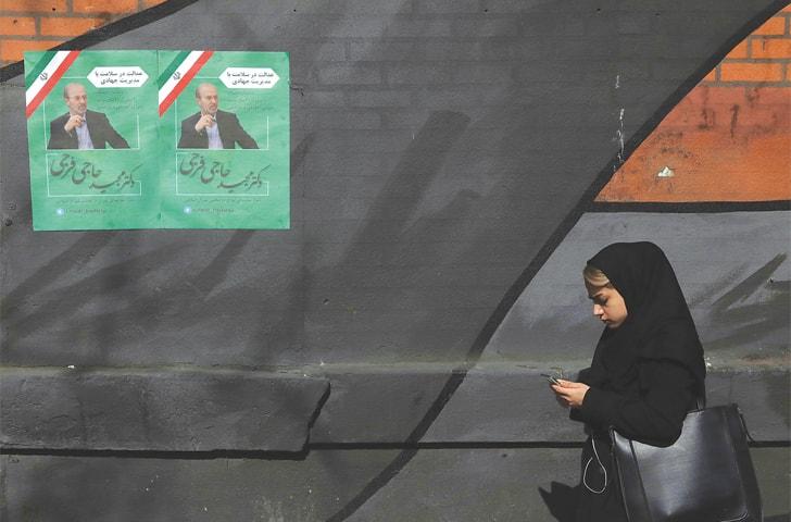 Tehran: A pedestrian walks past campaign posters for parliamentary election candidate Majid Hajifaraji on Thursday.—AP