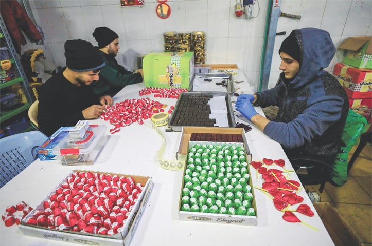 GAZA CITY: Workers wrap and pack chocolates at Al Arees factory.—AFP