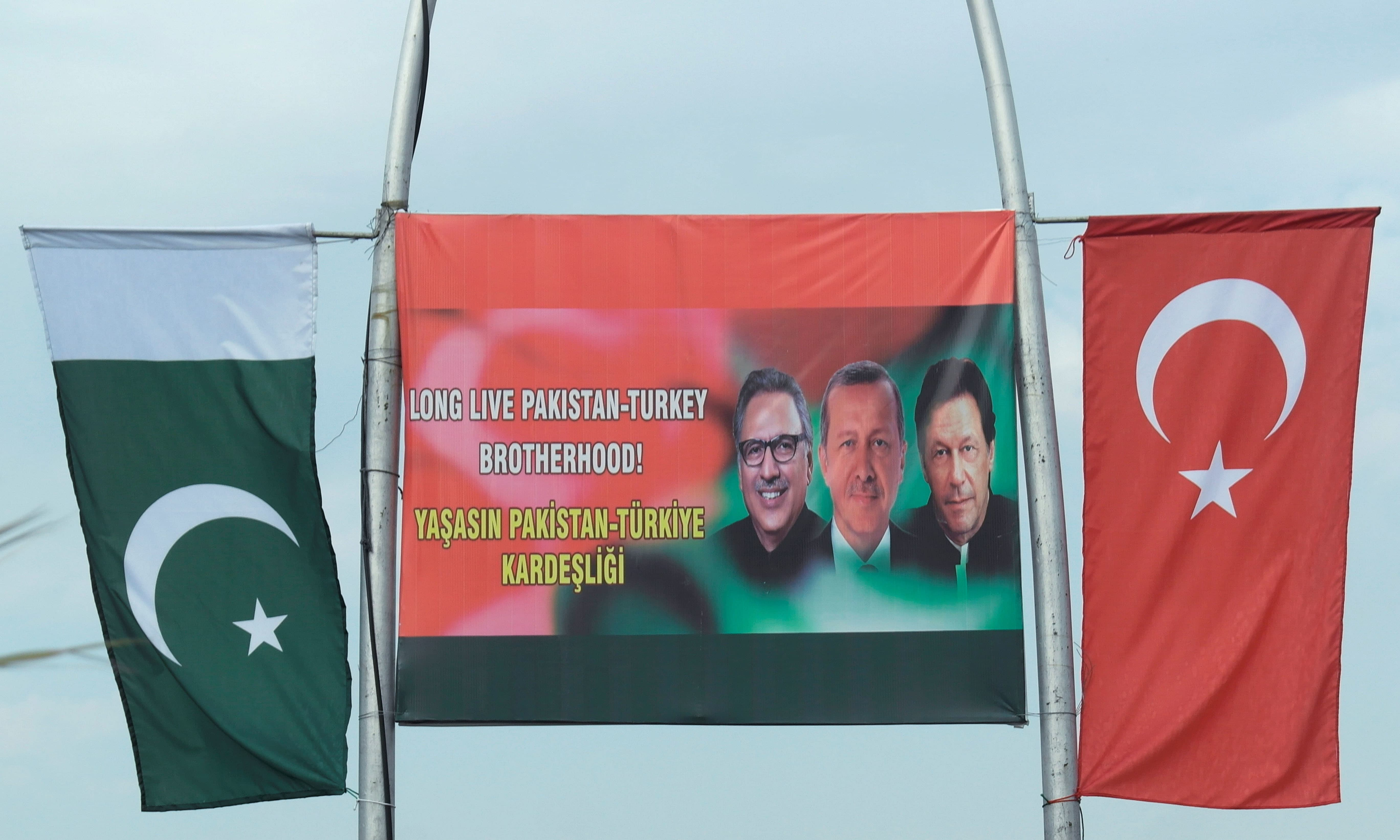 Pakistan and Turkey's national flags are seen on poles next to a sing showing President Arif Alvi, Turkish President Tayyip Erdogan and Prime Minister Imran Khan in Islamabad on February 13. — Reuters