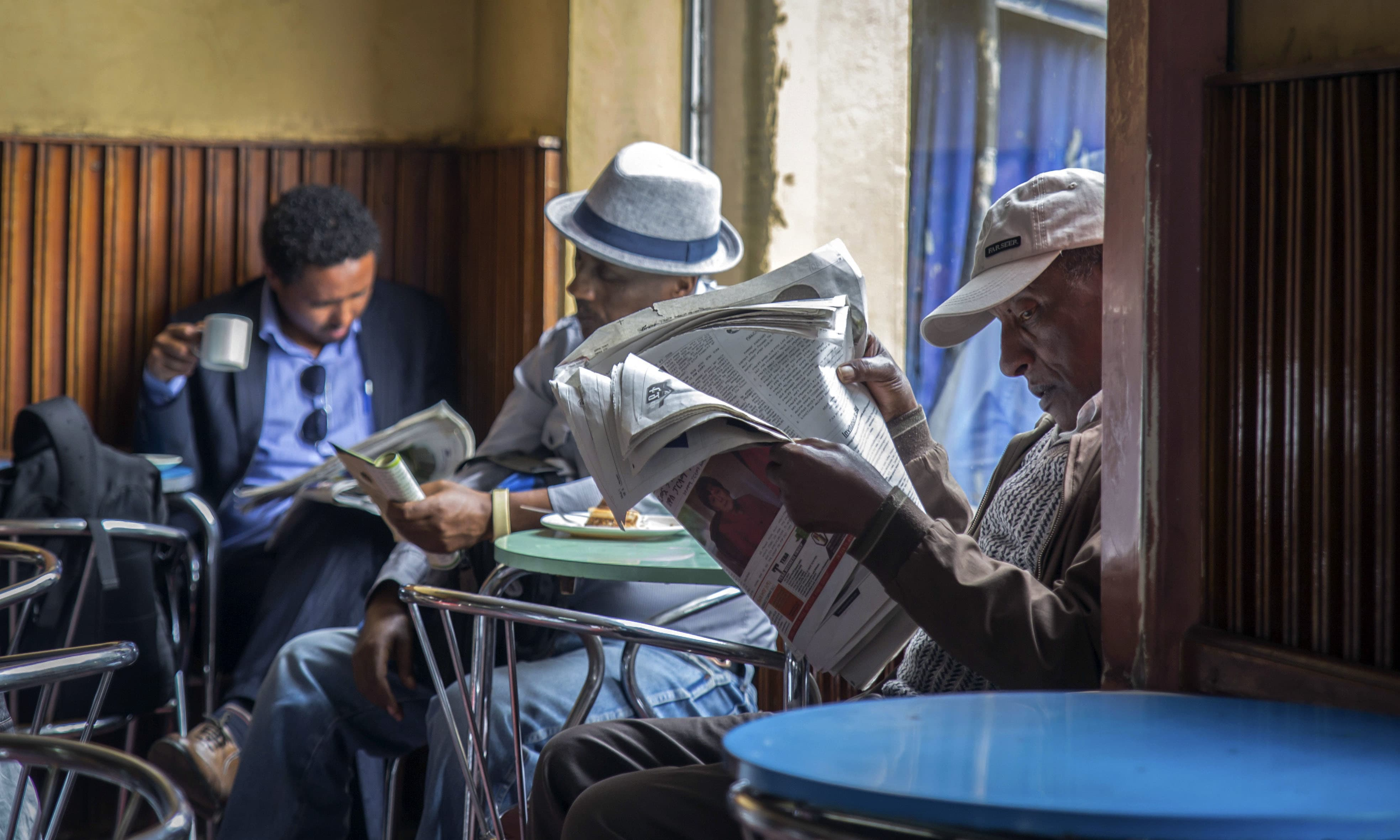 In this Monday, Oct. 10, 2016 file photo, Ethiopian men read newspapers and drink coffee at a cafe during a declared state of emergency and internet shutdown in Addis Ababa, Ethiopia. — AP