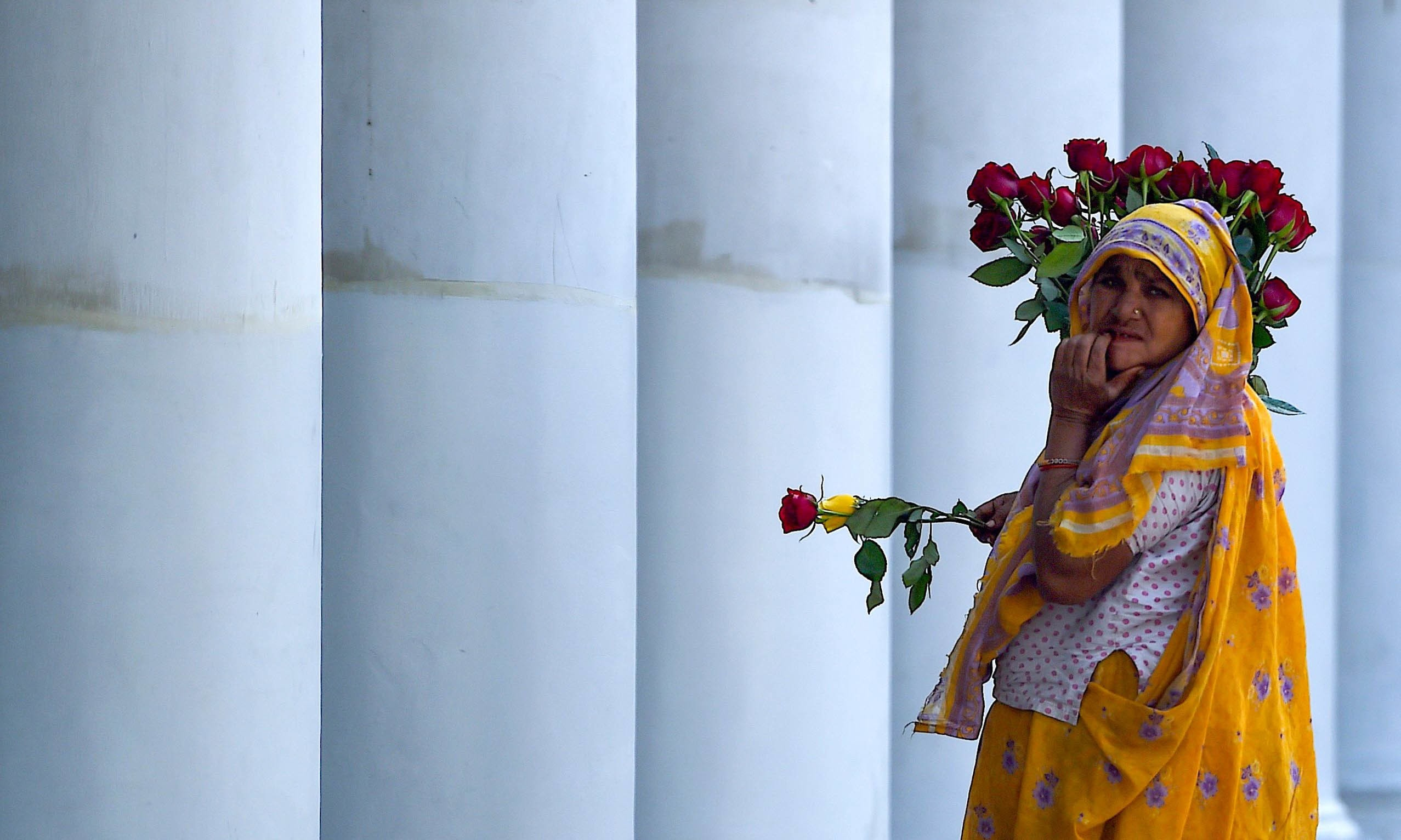 A woman selling roses looks for customers on the eve of Valentine's Day in New Delhi. — AFP