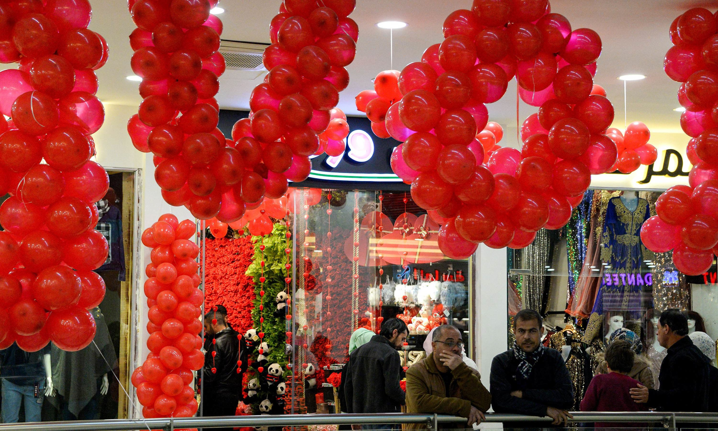 "Men stand underneath red balloons arranged to read in English ""LOVE"" as people shop for Valentine's gifts at a shopping mall in Iraq's northern city of Mosul on February 13. — AFP"
