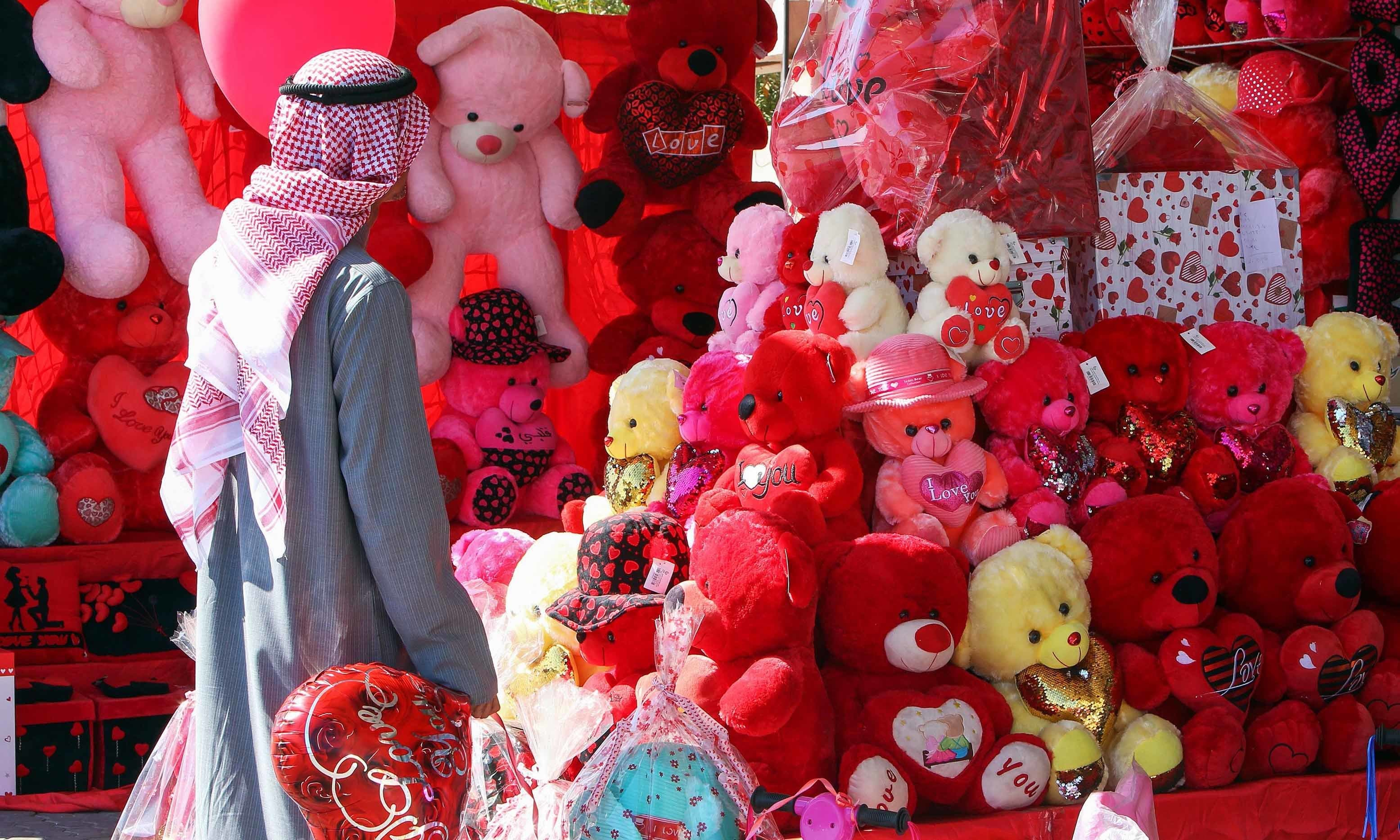 A Kuwaiti man holds a heart-shaped balloon outside a shop in Kuwait City on February 13 ahead of Valentine's Day. — AFP