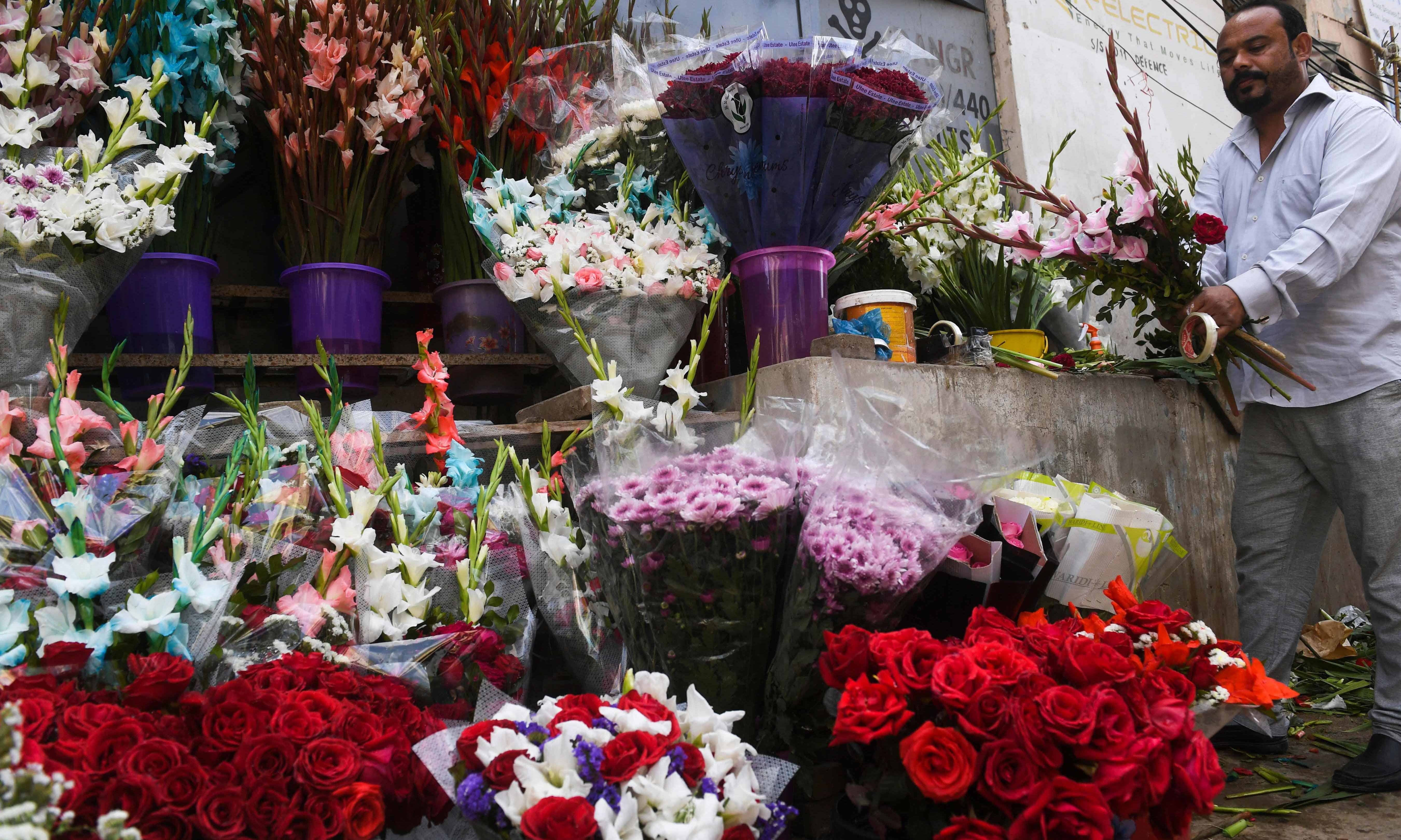 A vendor prepares a flower bouquet at a roadside stall ahead of Valentine's Day in Karachi on February 13.