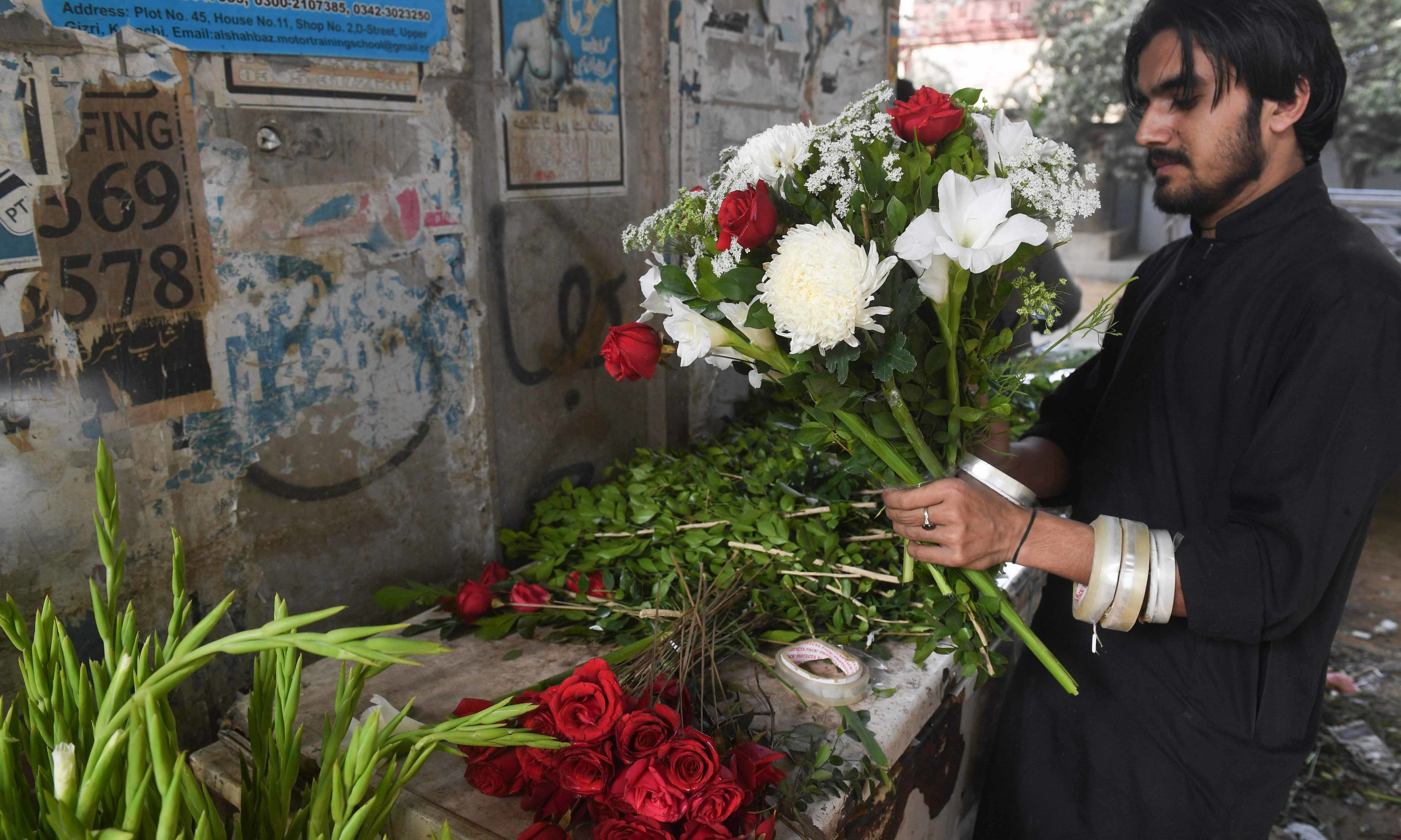 A vendor prepares a flower bouquet at a roadside stall ahead of Valentine's Day in Karachi on February 13. — AFP
