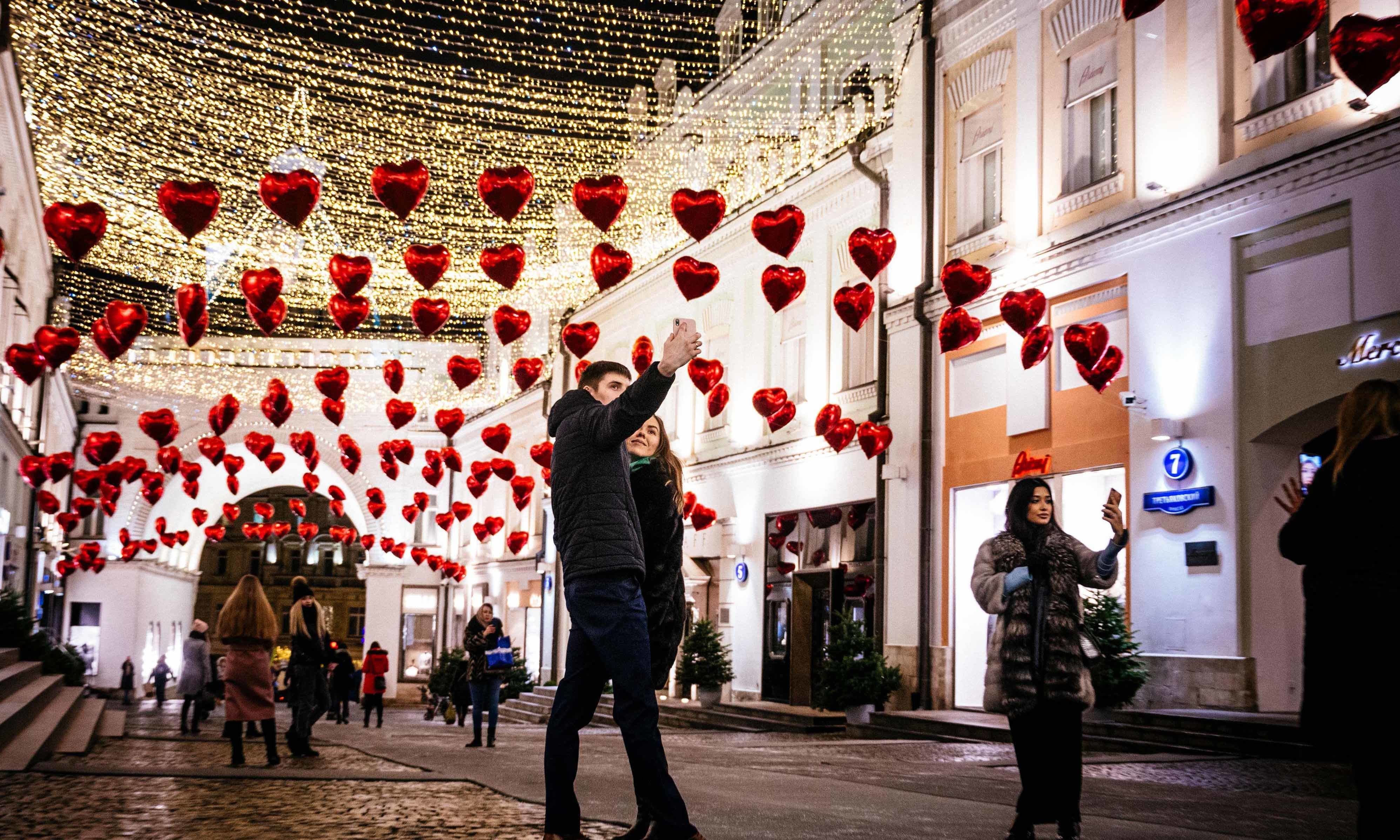 People pose for a selfie under heart-shaped balloons displayed on the eve of Valentine's Day in downtown Moscow on February 13. — AFP
