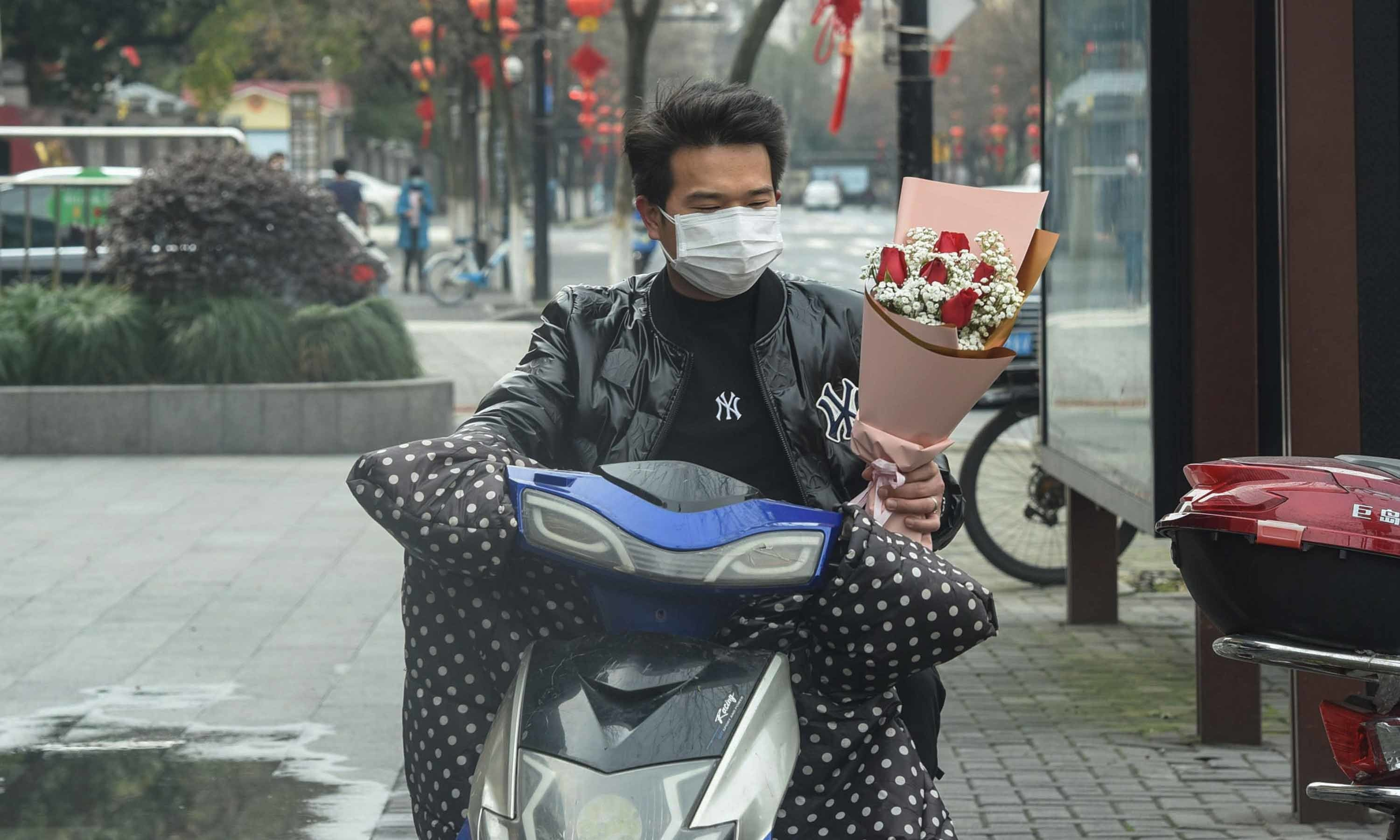 A man holds a bouquet of roses as he leaves a flower shop in Hangzhou in China's eastern Zhejiang province on February 14. — AFP