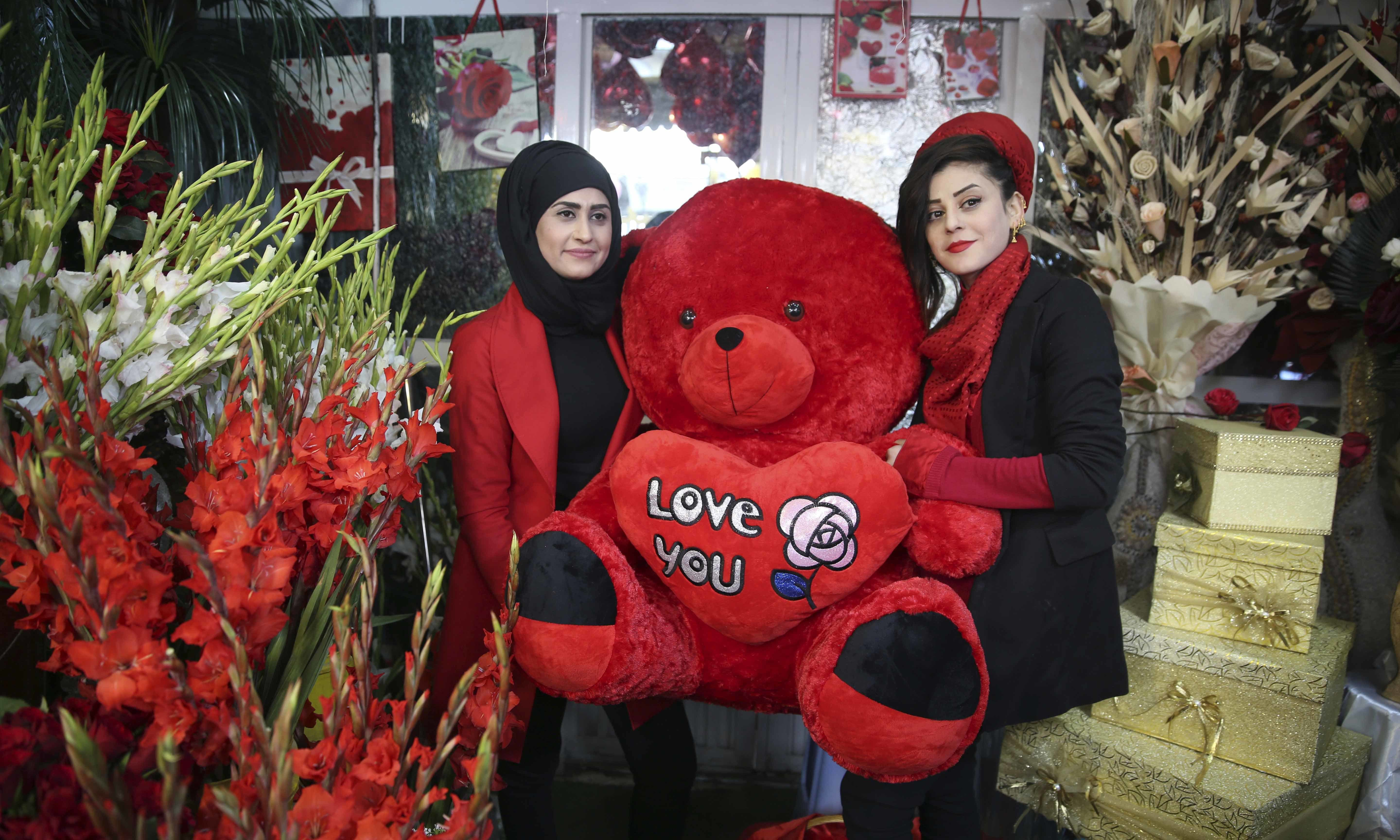 Women hold a teddy bear as they pose for a photograph inside a flower shop on Valentine's Day in Kabul, Afghanistan on Friday. — AP
