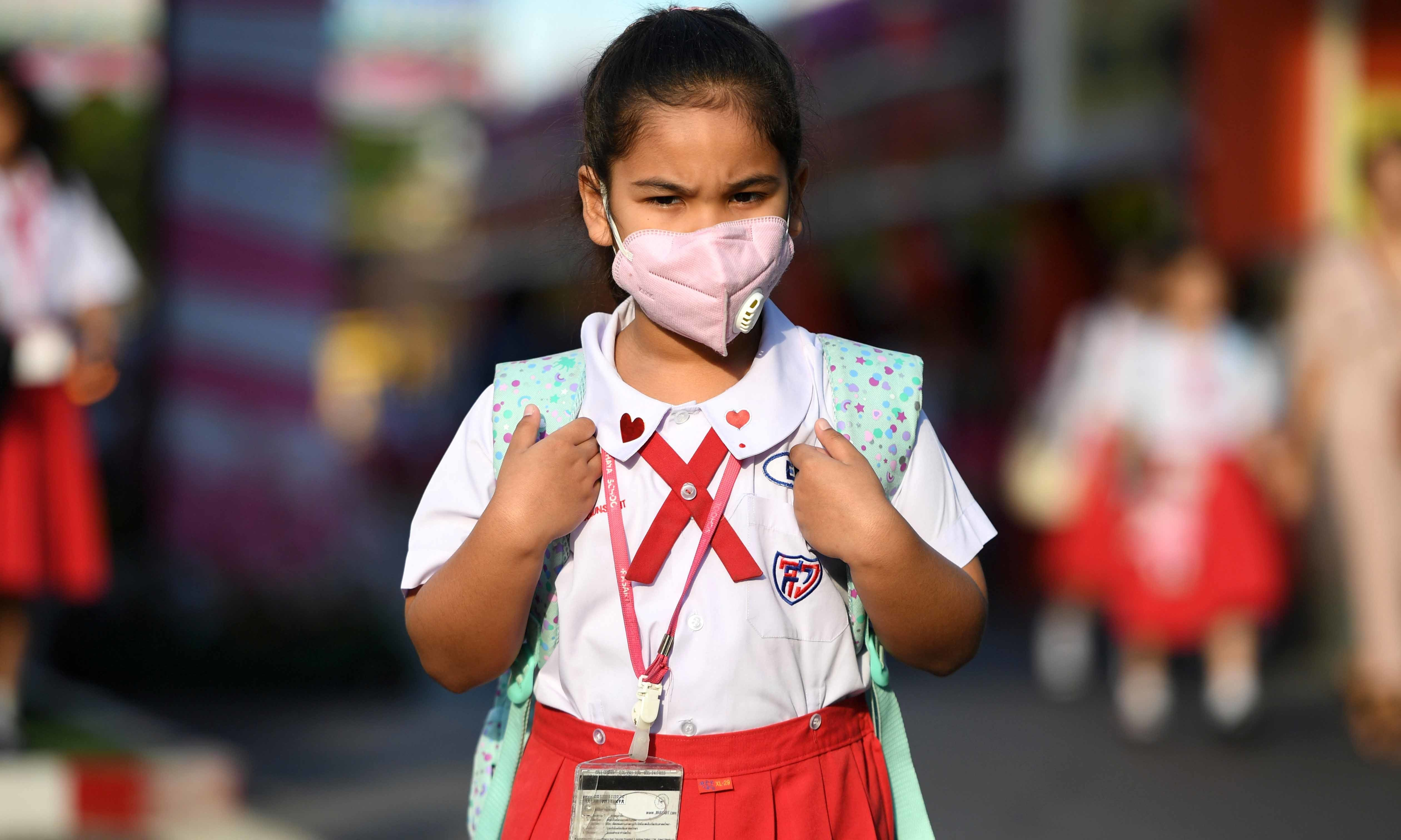 A girl arrives to school wearing a protective mask on Valentine's Day in Ayutthaya, outside Bangkok, Thailand on  February 14. — Reuters