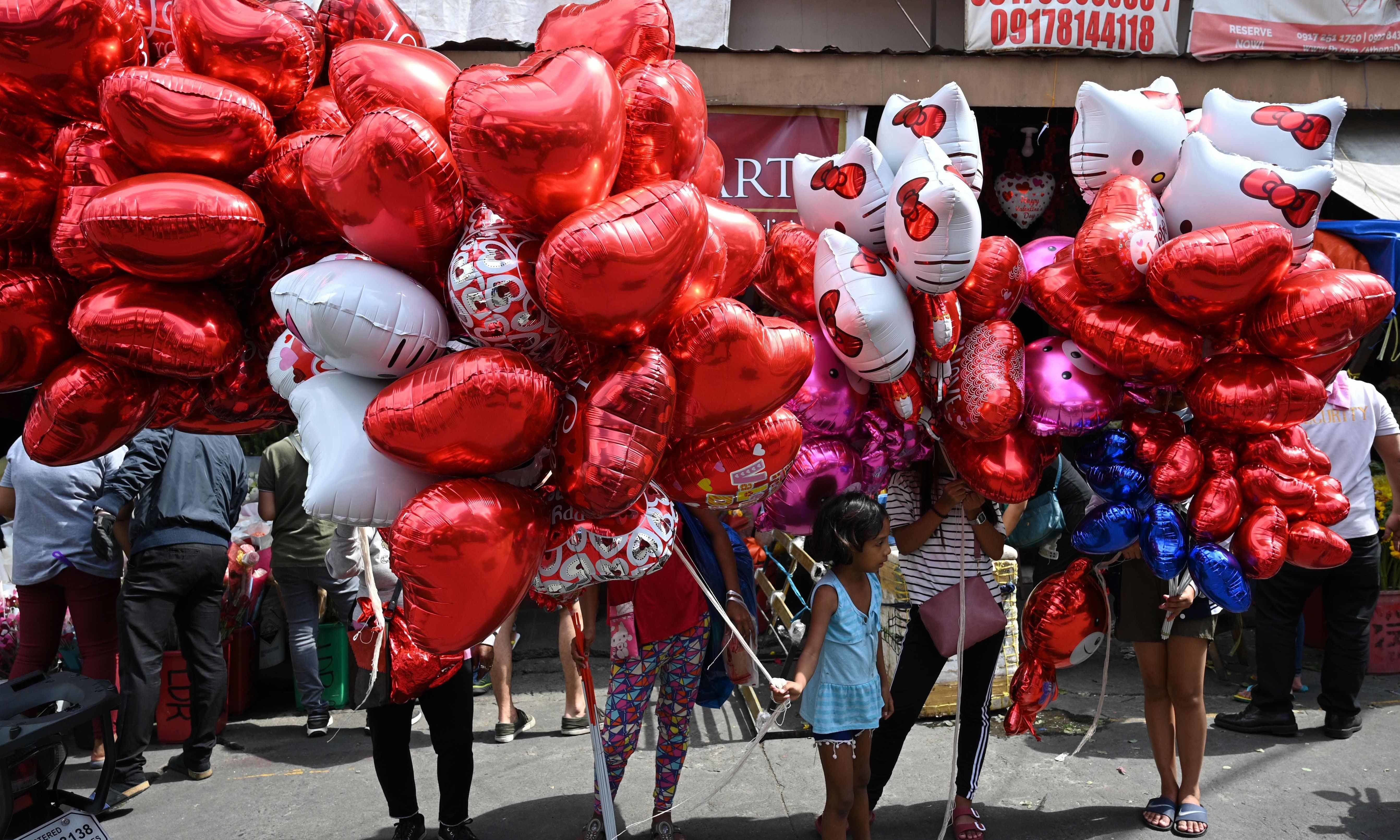 Vendors selling heart-shaped balloons wait for customers on Valentine's Day at a flower market in Manila on February 14. — AFP