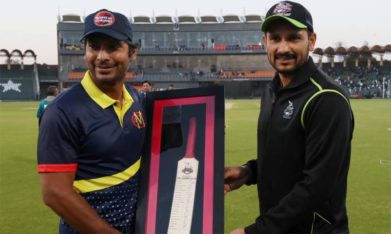 Marylebone Cricket Club captain Kumar Sangakkara is presented by a signed bat by Lahore Qalandars skipper Sohail Akhtar. — Photo courtesy AFP/24 HD