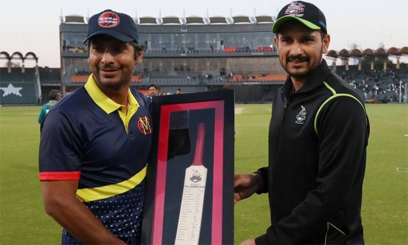 ایم سی سی کے کپتان سنگاکارا ٹیم کے کھلاڑیوں کا دستخط شدہ بیٹ لاہور قلندرز کے کپتان کو دے رہے ہیں — فوٹو: اے ایف پی