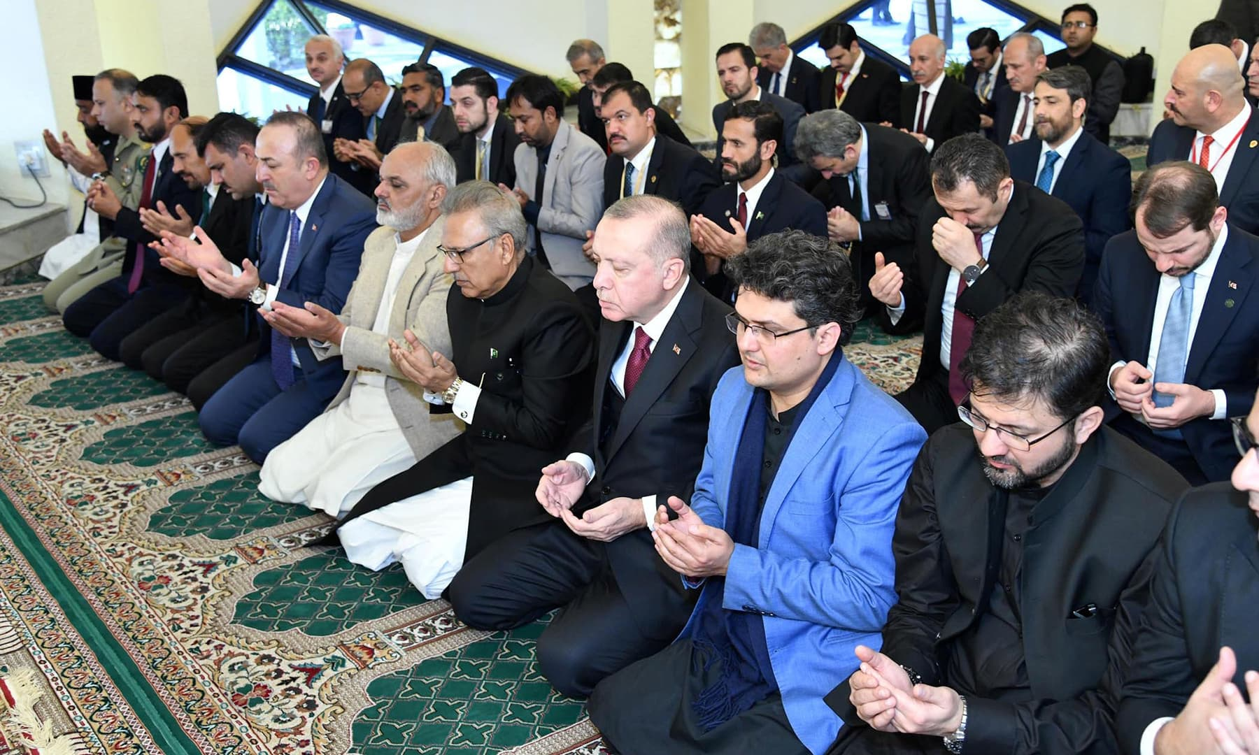 Turkish President Erdogan along with President Arif Alvi hold palms as they attend Friday prayers at President House in Islamabad. — Reuters
