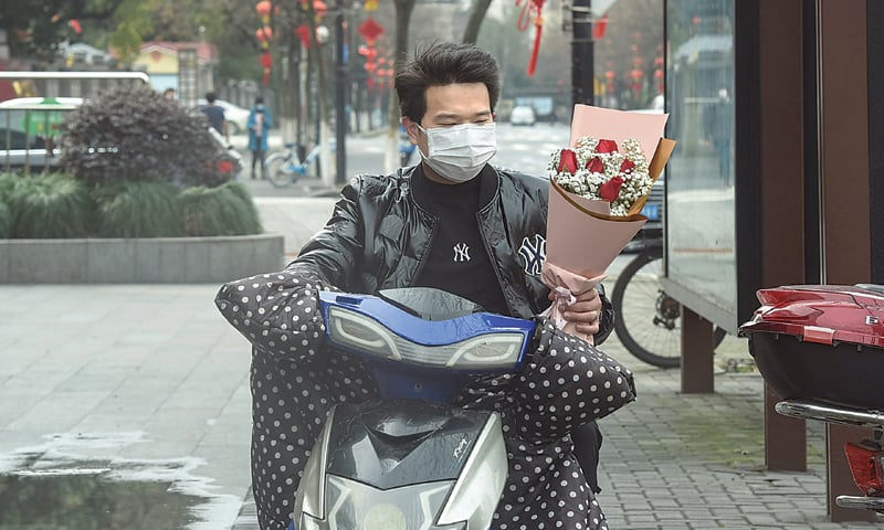 HANGZHOU (China): A man holds a bouquet as he leaves a flower shop on Friday. Couples around China settled for a quiet Valentine's Day in view of the deadly coronavirus outbreak in their country.—AFP