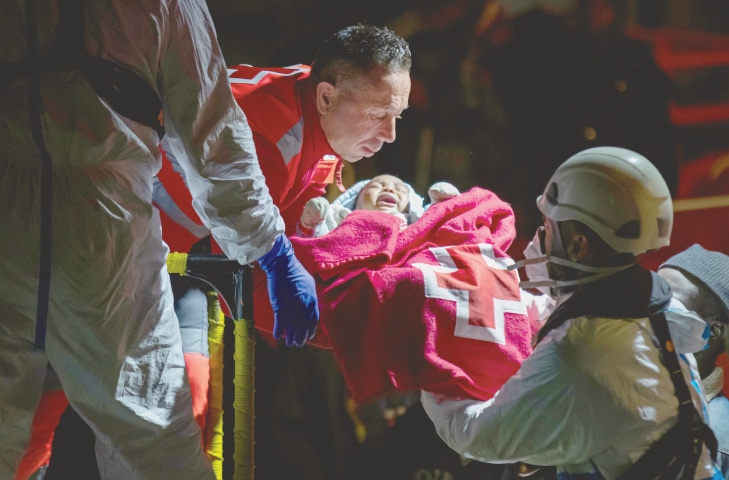 A baby is being taken by a rescue worker from a Spanish coast guard vessel after being born at sea near the port of Arguineguin, on the island of Gran Canaria, on Friday.—Reuters