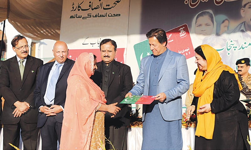 LAHORE: Prime Minister Imran Khan distributing Insaf Sehat Cards among beneficiaries at the Governor House on Saturday. Punjab Governor Chaudhry Mohammad Sarwar and Chief Minister Usman Buzdar are also seen.—Online