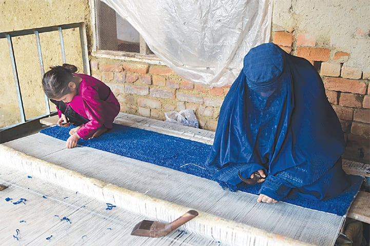 An Afghan refugee woman and her daughter make carpet at her home in a refugee camp in Peshawar.—AFP