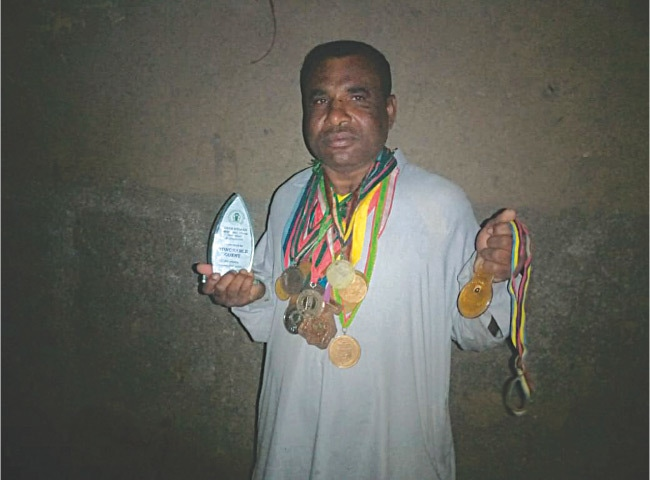 Allah Bux showing off their medals and awards