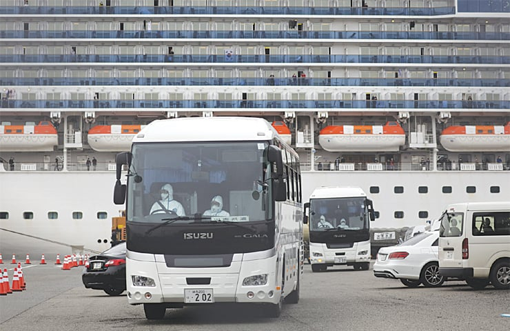 Yokohama: Two buses leave a port where the quarantined Diamond Princess cruise ship is docked. The US embassy said on Saturday that Americans will be removed from the cruise ship quarantined off Japan and flown home as dozens more cases of the new coronavirus were diagnosed on board. At least 285 people on the cruise ship have contracted the illness but hundreds of passengers and crew have not yet been tested as they wait in a quarantine that was scheduled to end Feb 19.—Agencies