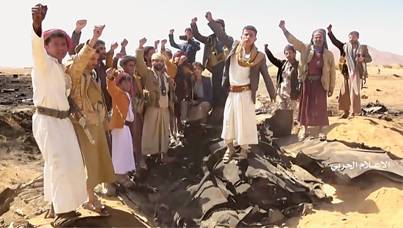 SANAA: Yemenis cheer at the site where a Saudi aircraft crashed following an air strike by Iran-backed Houthi rebels in Al Jawf province. The fate of the crew remained uncertain.—AFP