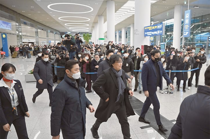 SEOUL: South Korean director Bong Joon-ho (centre right) walks past the media upon his arrival at Incheon airport on Sunday.—AFP